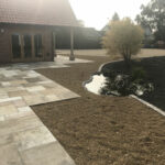 Rejuvenated pond area, surrounded by 10mm Golden Pea Shingle beds and Fossil Mint patio area