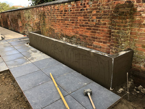 Raised concrete block retaining flower bed - Aylsham